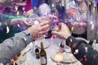 Hands clink glasses of champagne and candy. Celebrating a joyful event with a group of people.