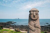 Dol hareubang stone grandpa sculpture and sea, Jeju Olle Trail in Jeju Island, Korea