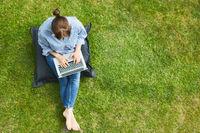 Frau als Freiberufler am Laptop im Sommer im Garten