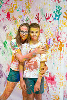 Portrait of a cute happy woman with her son painting and having fun