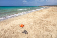 Beautiful wild beach with no tourists, crystal clear sea, but waste (plastic red bottle, black bag and other small debris) spoils the perfect picture. Ocean pollution concept.