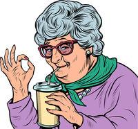 elderly woman granny drinks a coke drink, ok gesture