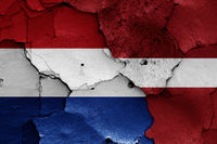 flags of Netherlands and Latvia painted on cracked wall