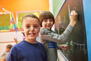 Kinder malen mit Kreide an der Tafel im Kindergarten