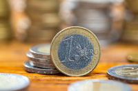 One euro coin standing on wooden table from close up.