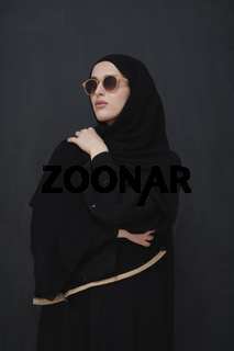 Young muslim in traditional clothes or abaya and sunglasses posing in front of black chalkboard