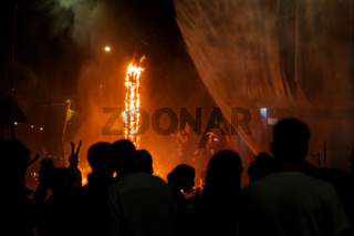 Silhouettes of visitors enjoying the water spray, which extinguishes the burning figurines for the Fallas festival in Gandia, Spain
