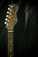 The neck and frets of a guitar on a black backgrou