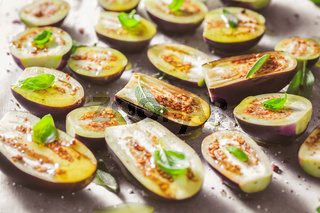 Small raw eggplants prepared for baking on baking sheet with herbs and spices