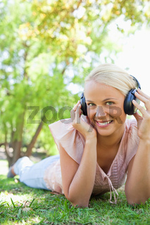 Smiling woman enjoying music on the lawn