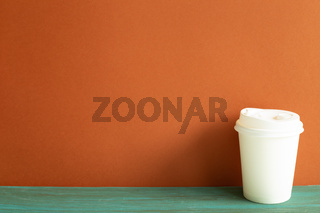 Disposable white paper coffee cup on green wooden table. red wall background