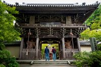 Visitors looking at the entrance with nio kings statues at Daisho-in temple, Miyajima, Japan
