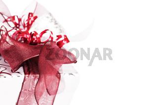 silbernes weihnachtsgeschenk mit roten geschenk bändern