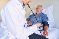 Arzt oder Krankenpfleger beim Blutdruck messen