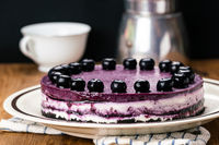 Side view of delicious homemade blueberry cheesecake garnished with preserved blueberry.