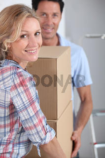 Couple carrying packing boxes into new home