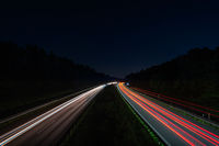 Lighttrails of a traffic motorway from the cars front and headlights, passing fast the point ov view.