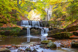 Old Stone Arch in the Summer Forest and Natural River Rapids