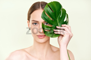 Close up portrait of beautiful young woman covering her eye with monstera tropical leaf