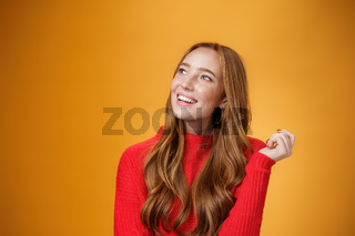Close-up shot of nostalgic cute and sensual friendly-looking european female with nice cute memories looking at upper left corner dreamy and delighted, imaging and picturing desire over orange wall