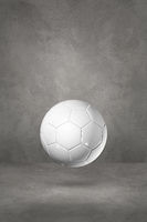 White soccer ball on a concrete studio background