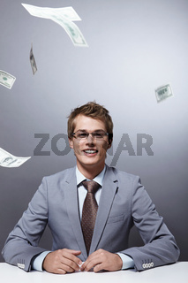A young businessman wearing glasses on the background of flying money