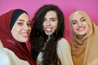 Muslim women taking selfie by mobile phone isolated on pink background
