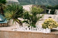 White wood lettering WEDDING with candles outside.