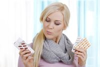 Frau wählt unter verschiedenen Tabletten aus