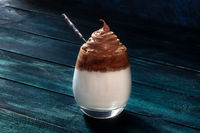 Dalgona cold coffee in a glass with a spoon, on a dark blue background