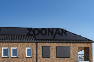 Newly build houses with solar panels attached on the roof against a sunny sky Close up of new building with black solar panels. Zonnepanelen, Zonne energie, Translation: Solar panel, , Sun Energy