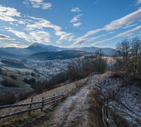 Winter coming. Last good weather days in autumn mountain countryside morning picturesque scene. Dirty road from hills to the village. Hoverla and Petros Ukrainian Carpathians mountains in far.