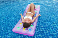Woman on air mattress in swimming pool