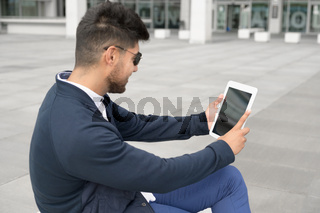 Shot of man using tablet with blank screen on street