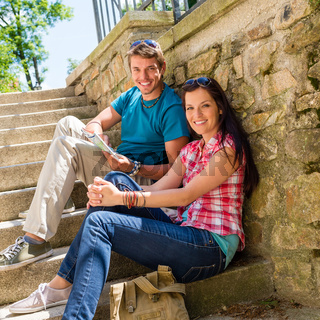 Happy young couple sitting on stairs smiling