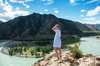 Woman in blue dress on the confluence of two rivers Katun and Chuya
