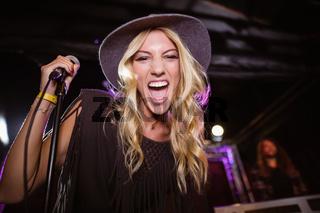 Portrait of cheerful female singer performing at nightclub