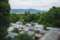Aerial view over the roofs and five-story pagoda surrounded by forest of Miyajima, Japan