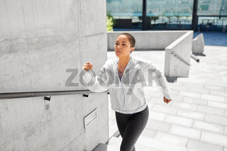 african american woman running upstairs outdoors