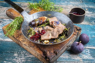 Traditional cooked sliced veal tongue figs and cranberries offered as close-up in a rustic cast-iron skillet on an old wooden board