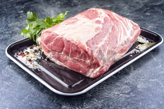 Modern style traditional raw corned pot pork roast with herbs offer offered as close-up on a rustic metal tray