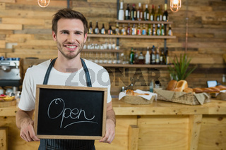 Portrait of smiling waiter standing with open signboard at counter