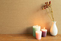 Candles and vase of dry flower on wooden table. brown wall background