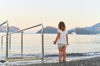 Toddler girl standing alone on the sea beach in sunset light. Close to nature childhood activities. Slow mindful living. Ecology education for kids. Great outdoors concept