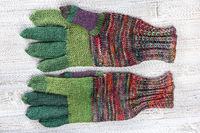 palm side of hand knitted woolen gloves on gray