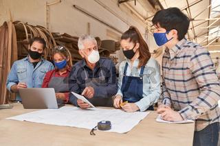 Handwerker Team mit Mundschutz in Besprechung