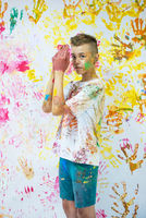 Portrait of a cute happy boy painting and having fun