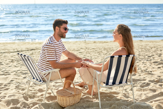 happy couple sitting in folding chairs on beach