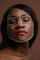 Close-up portrait of attractive black woman with pearls on her face. Vertical.