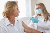 Doctor administering a vaccine on an elderly patient